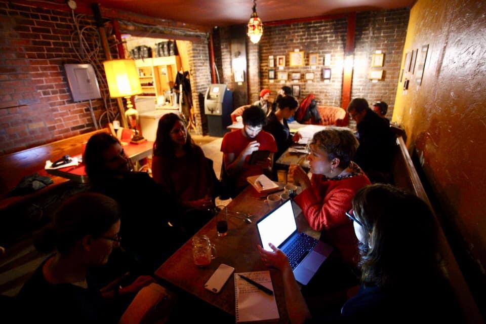 Membres du Café des savoirs libres discutant de libre-échange marchand et de restriction du droit d'accès culturel dans un bar sombre, le visage éclairé par leurs écrans numériques, le 13 octobre dernier.